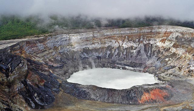 looking down at the Poás Volcano crater with steam rising off of the water