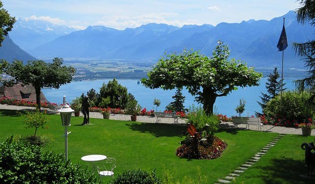 lush green garden area with flowers and trees on the edge of Lake Geneva