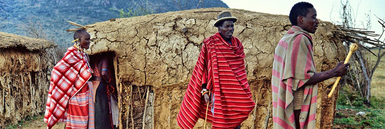 three members of the Maasai dressed in their distinctive bright clothing in front of their mud huts in Kenya