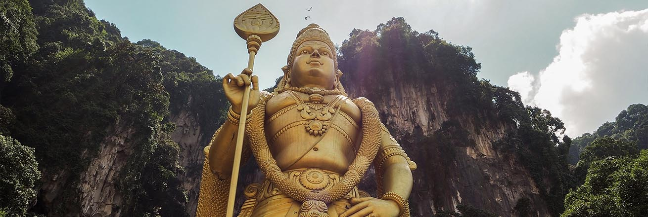 looking up at a large Golden Hindu statue in one of the caves in Kuala Lumpur