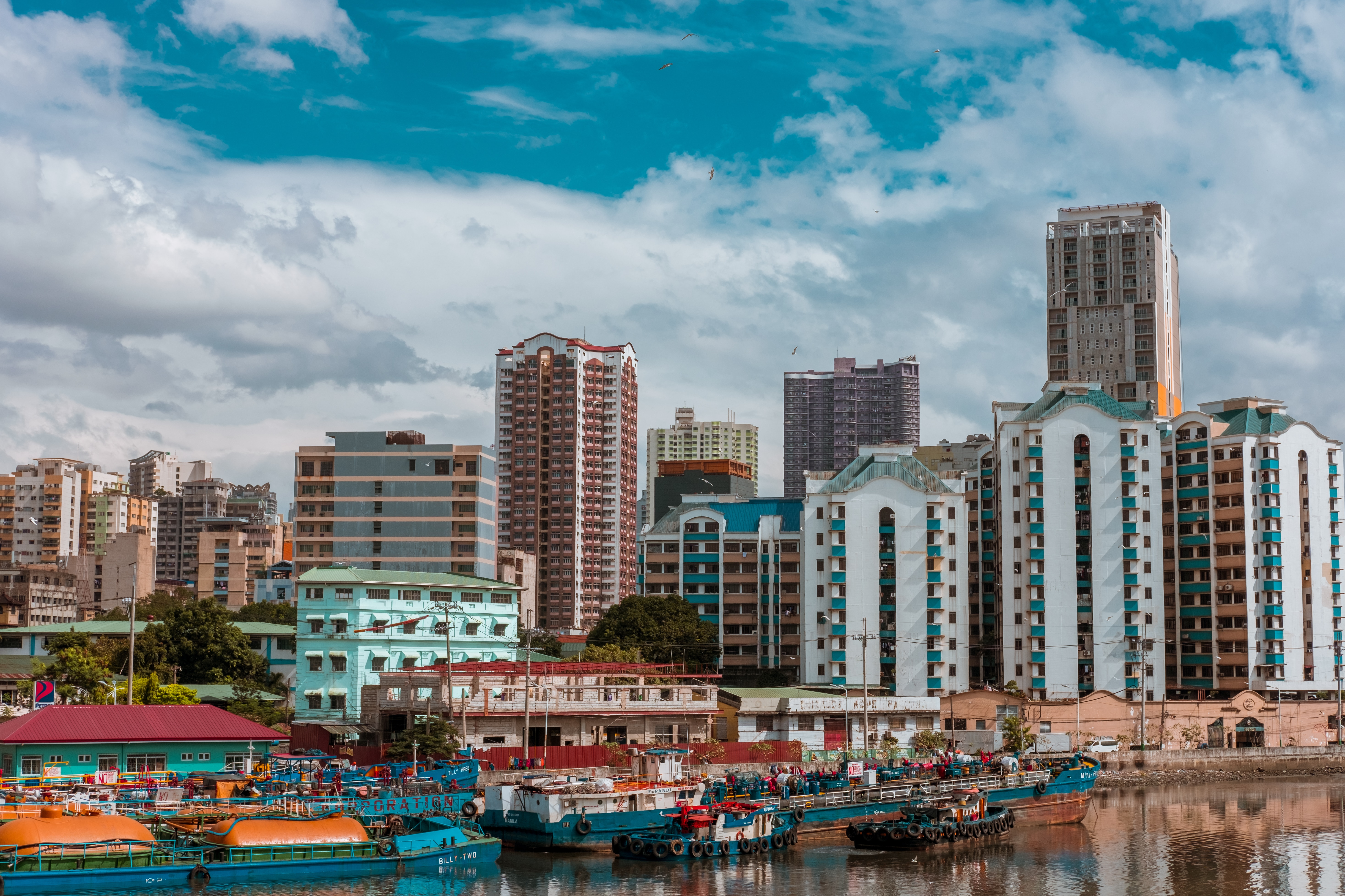 Waterfront view featuring boats and office buildings in Manila.