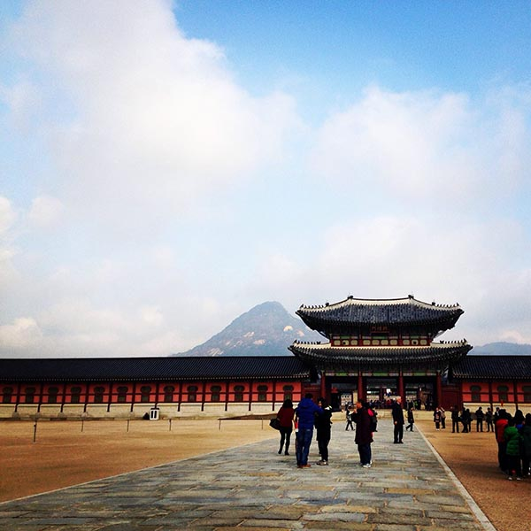 visitors walk outside of the onate Gyeongbokgung Palace in South Korea with mountains in distance