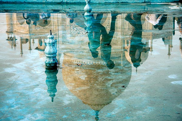reflection of the Taj Mahal in a giant puddle on the ground