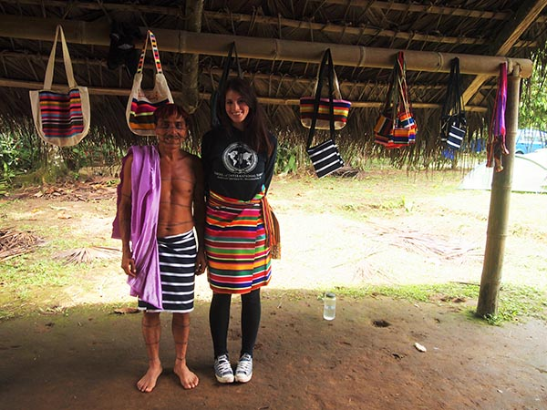 Jessica Walton stands next to the president of an indigenous Ecuadorian village. Colorful handmade bags hang behind them