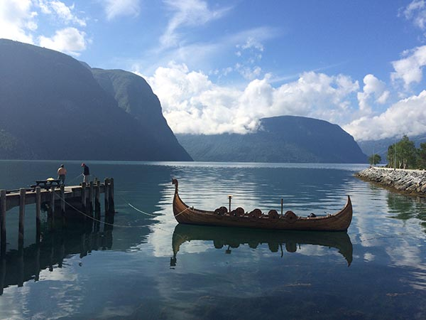 viking ship floats in the water with mountains in the background
