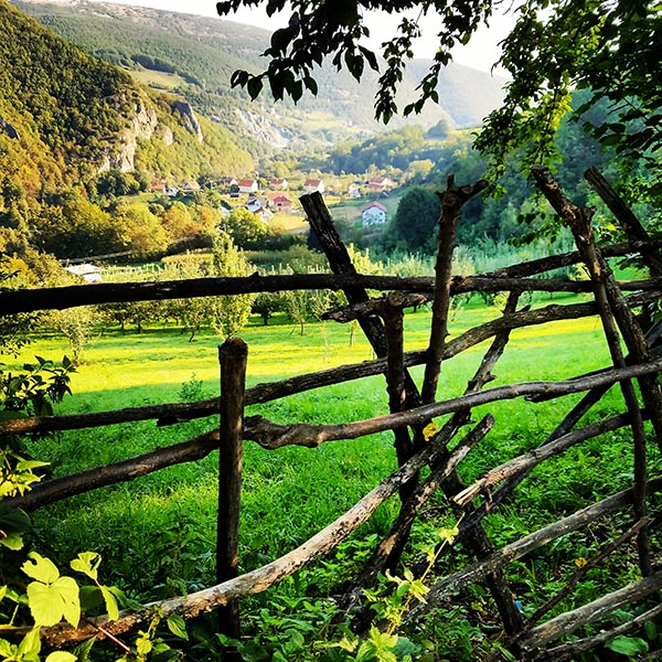 lush green grass and wooden fence built by hand overlooking the city of Brod, Kosovo