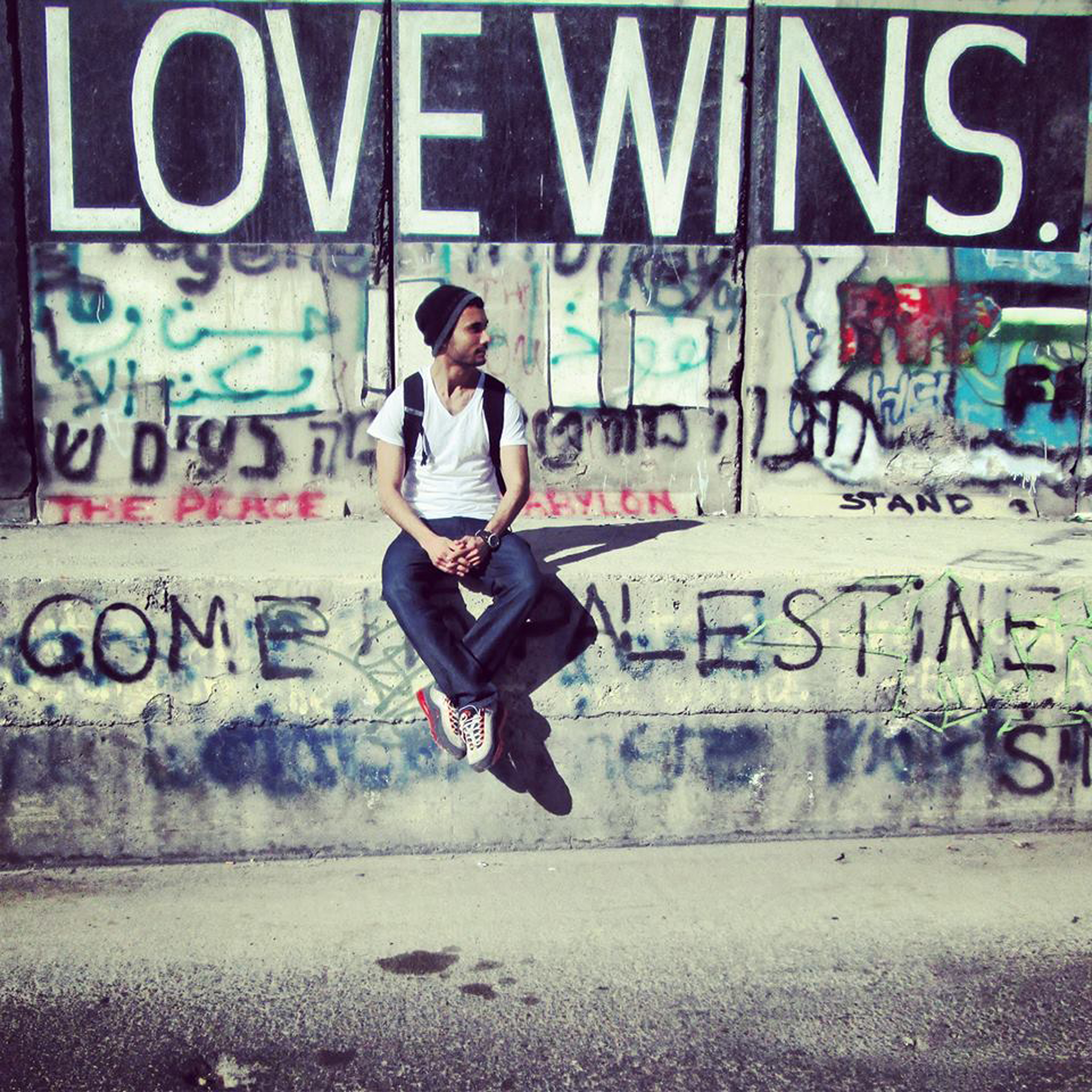 Image of SIS student sitting in front of graffitied wall in the West Bank