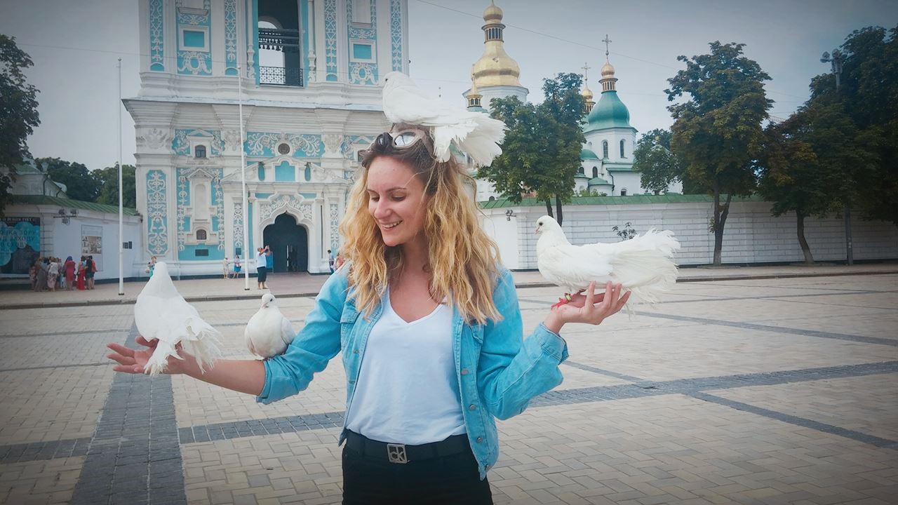 Student stands with doves in front of a church in Ukraine, Example of 2016 photo contest submission.