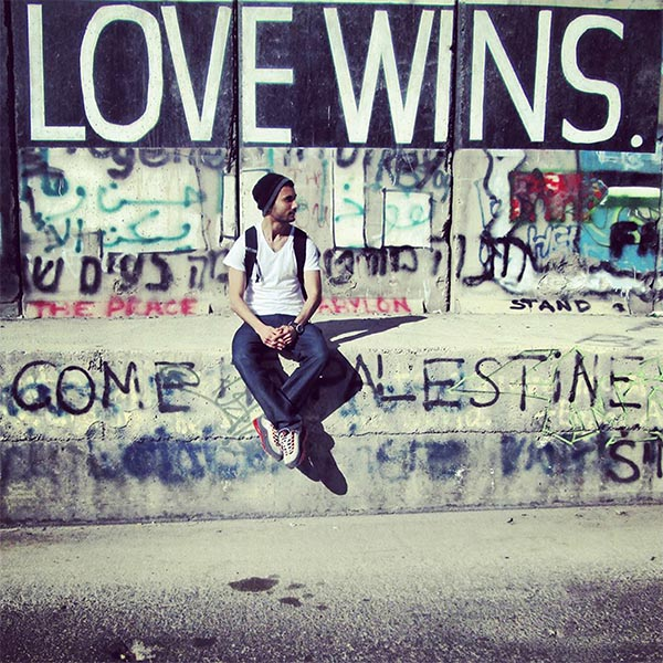 SIS student sitting in front of a graffiti wall in the West Bank -Love Wins is prominent in the graffiti