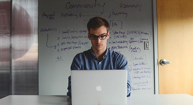 guy typing on laptop with words on a whiteboard behind him as he plans for a startup company