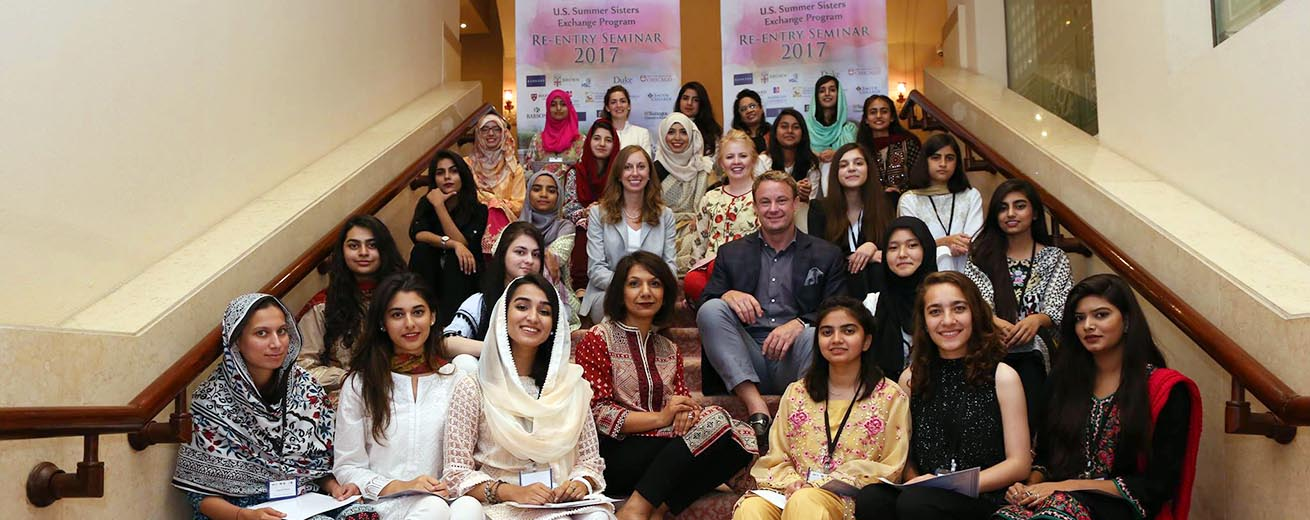 participants and staff from the Summer Sisters Exchange program from the US and Pakistan sit on the stairs