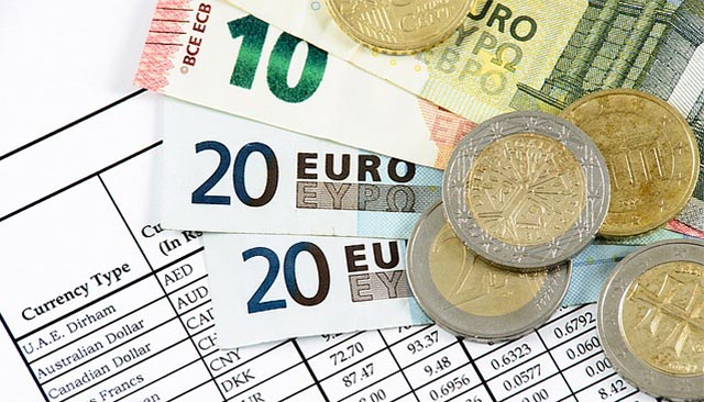 Euros and other currency lay on a sheet listing the currency types for exchange