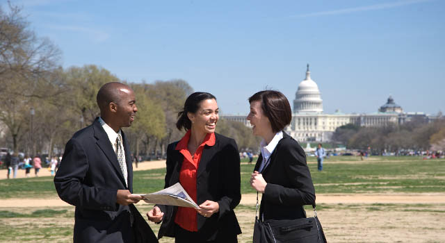 A diverse group of three people stand talking on the Washington Mall in front of the U.S. Capitol