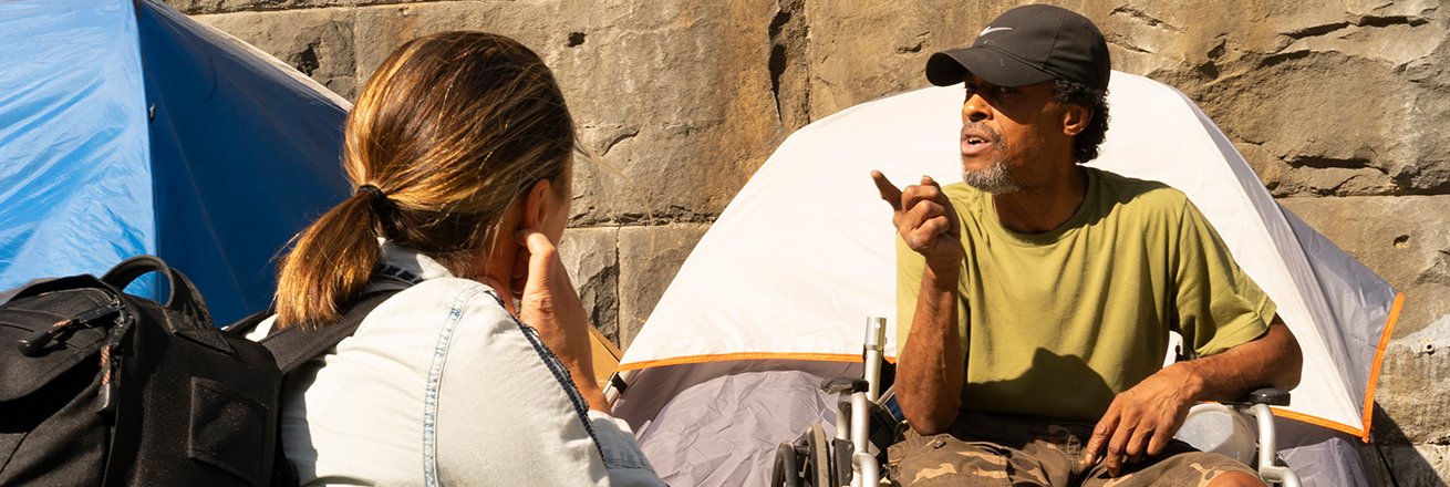 A woman interviewing a homeless man in front of a tent