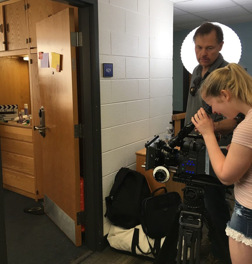 Students film the inside of a dorm room with a large movie camera