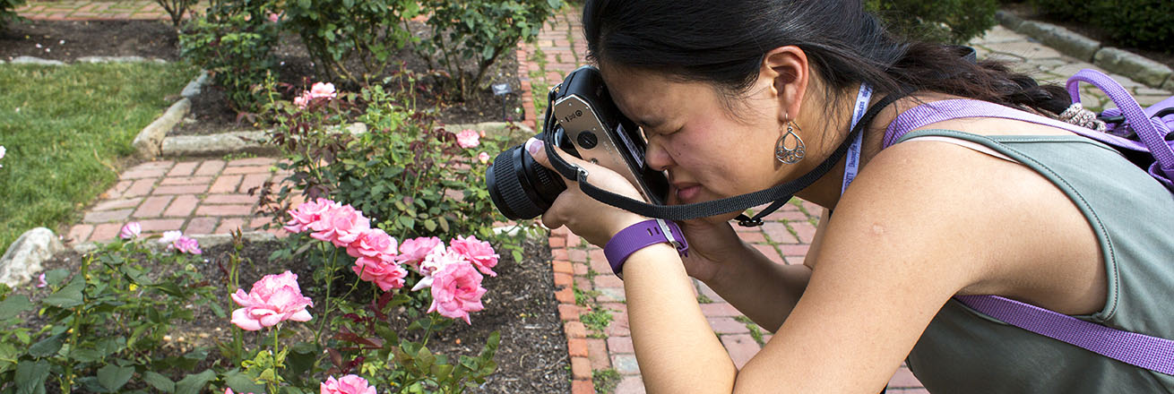 A discover the world of communication student photographs roses outside with a film camera