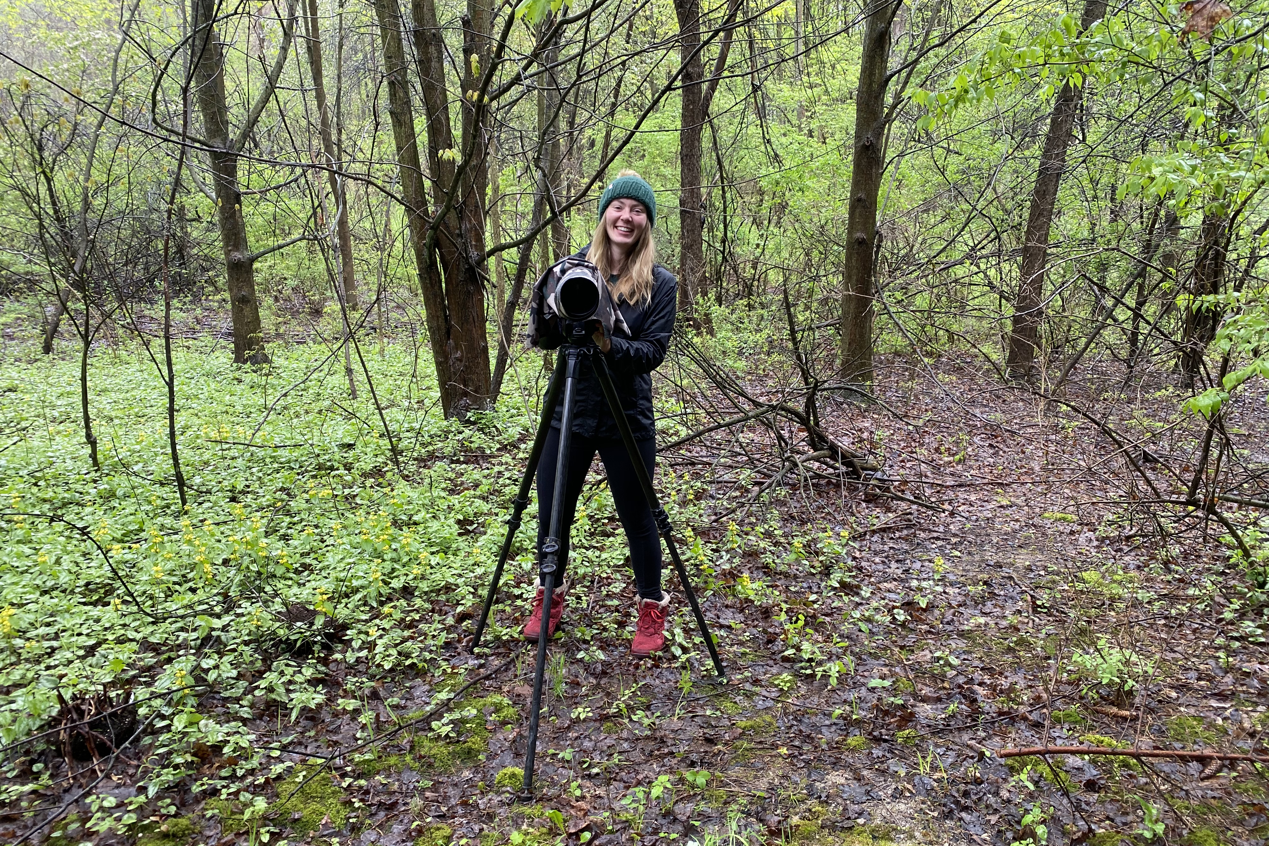 Female student stands in forest with camera