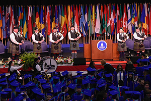 Commencement ceremonies featuring a bagpipers on the stage
