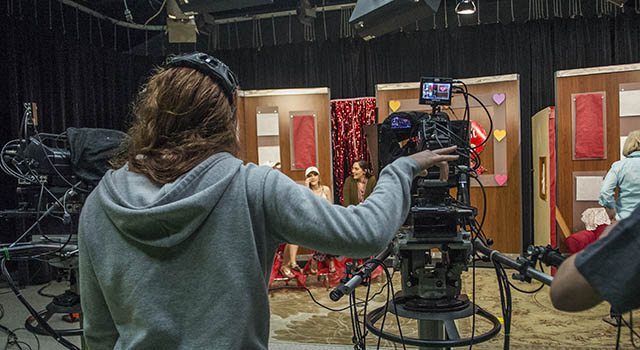 A female student directs during a TV production class