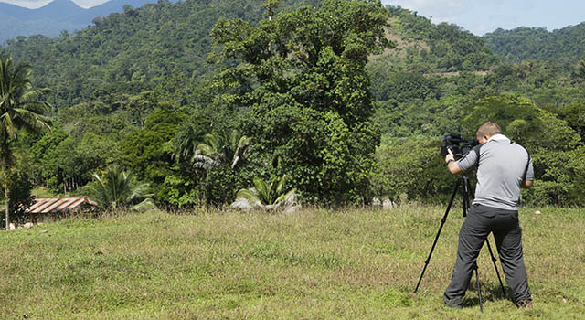 A man films in a tropical climate