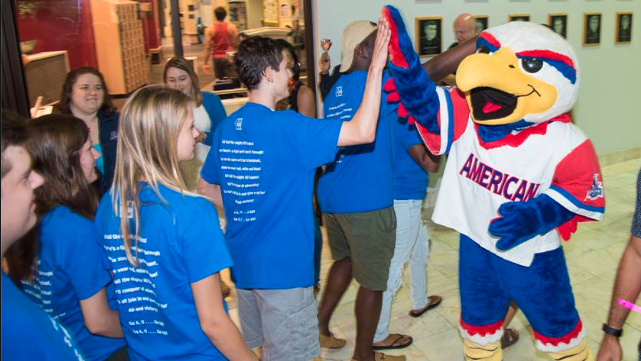 American Unievrsity mascot Clawed the Eagle high-fives incoming students at convocation.
