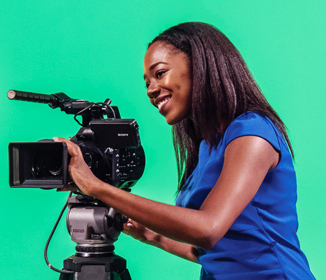 Shayla Racquel with camera in front of green screen