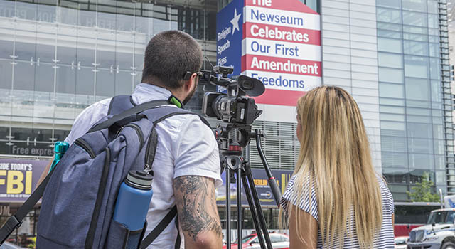 View from behind of two students filming the exterior of the Newseum.