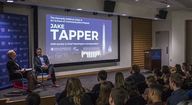 CNN Anchor Jake Tapper and SOC professor Jane Hall speak in front of an audience of students.