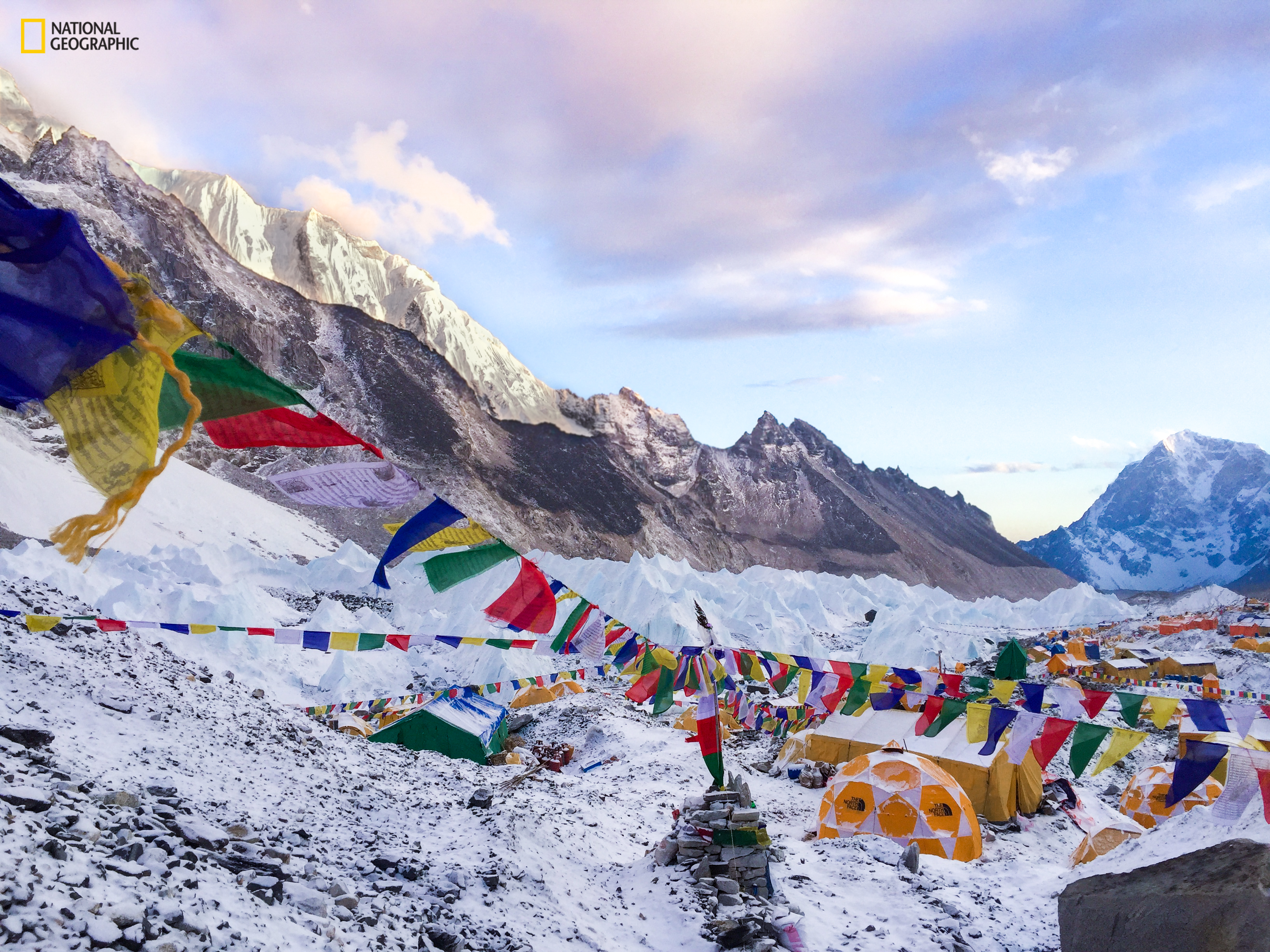 A snowy rocky landscape dotted with small tents and rows of colorful Nepalese prayer flags strung between them