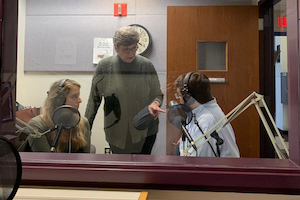Jill Olmstead standing over two students in an audio recording studio