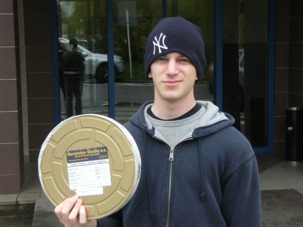 Charlie Watchel holding a film reel of his final project made during the AU Prague Aboard program.