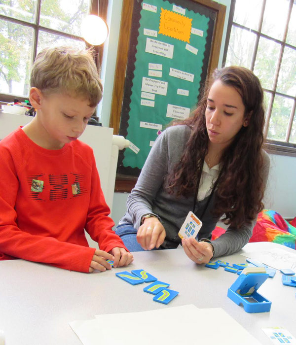 Young student playing a pattern-matching game with teacher.