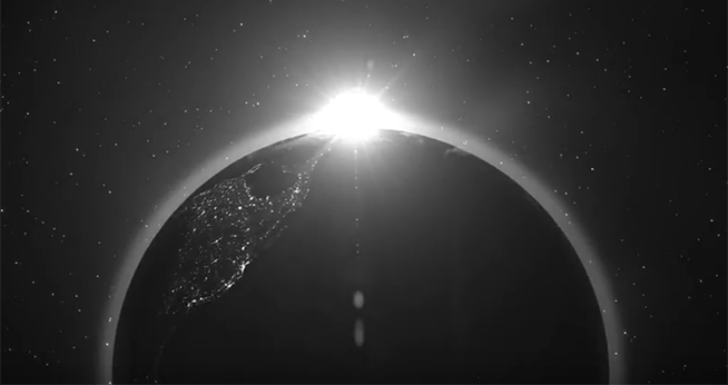 Black and white image of the sun rising above the rotating Earth.