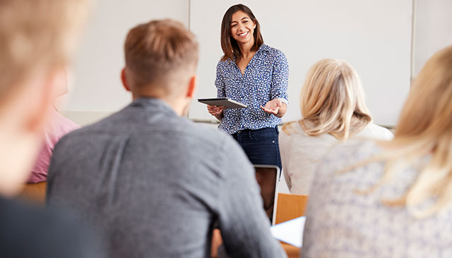 Woman speaking to students in classroom
