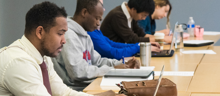 Students working at their computers and taking notes.