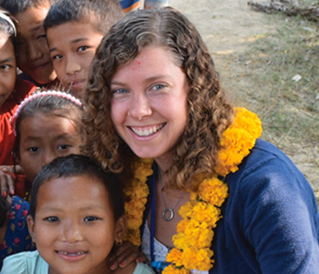 Sarah Riczo, center, joined by young students abroad.