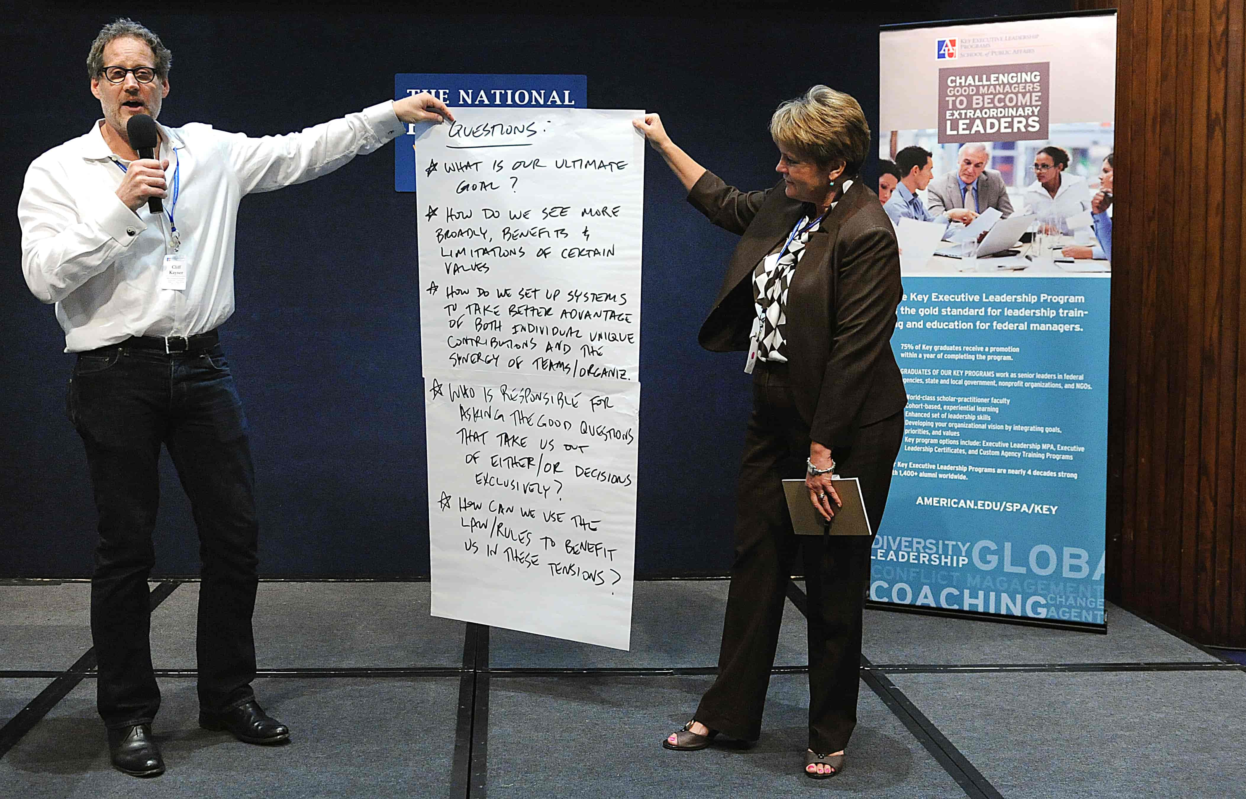 Two people hold a piece of paper that lists questions that will be answered during the conference.