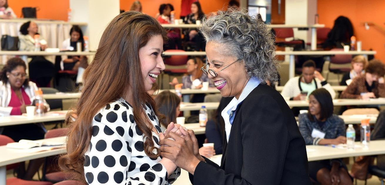Gwen Sykes talking with an attendee at the Women in Leadership Forum