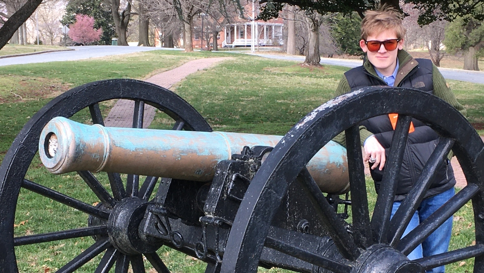 Student posing with cannon