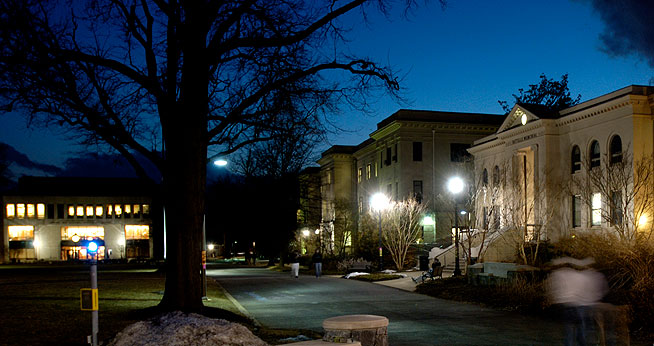 Photo of the quad on American University and the surrounding buildings lit up against a night sky