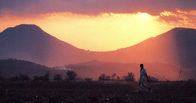 Nicaraguan man walking with sun setting behind mountains in the background