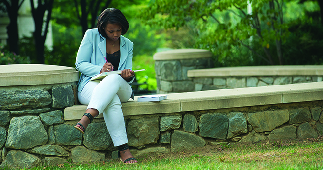 A lady works diligently while sitting outside on the AU campus.