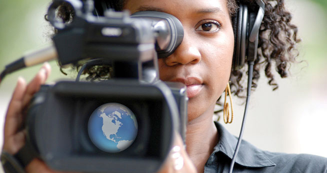 School of Communication student with video camera, graphic of earth in lens