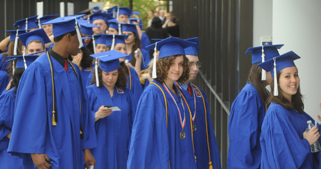 Students in caps and gowns in line at graduation