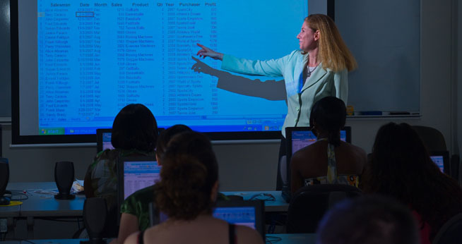 SIS professor instructs her students using a projector.