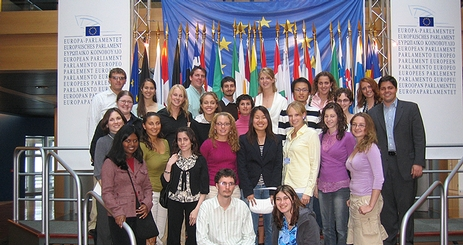Students at the European Parliament, standing in front of flags.
