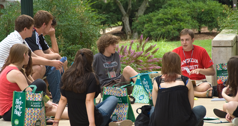 A group of new students sit on the quad accompanied by an Orientation Leader.