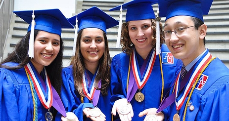 A group of four alumni of the FDDS program in graduation gowns.