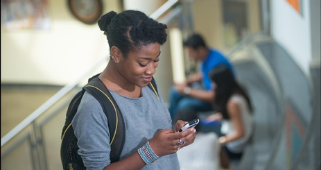 Cover of Annual Report with Student Checking Mobile Device