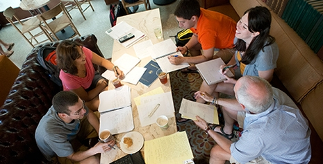 A group of five men and women engaged in a study group.  They are gathered around a table with notes and snacks.